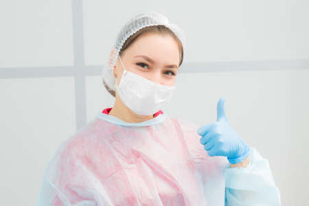 portrait of positive female doctor in mask and medical cap