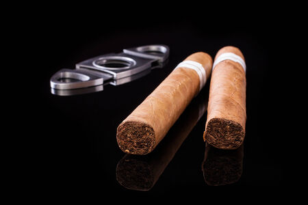 Cuban cigars and cutter isolated on black background photo