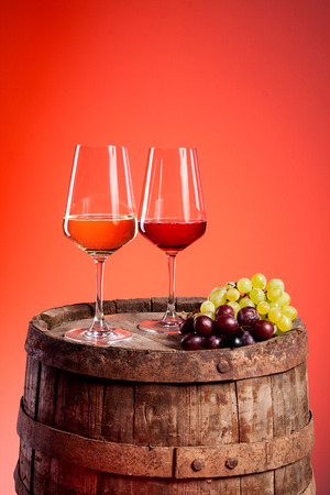 Two wine glasses on a wooden barrel with some grapes photo