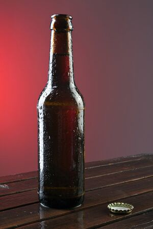 dewed: Opened beer bottle on a wooden table with a gradient red dark background