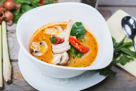 traditional spicy Thai Tom Yam soup on a wooden table with vegetables and herbs photo