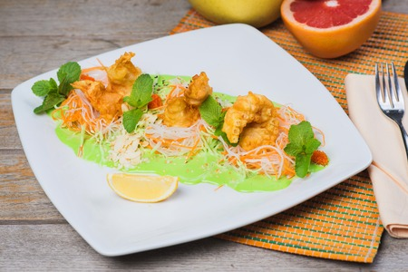 Fried breaded shrimp served with lettuce and vegetables on white plate on a table in a restaurant photo