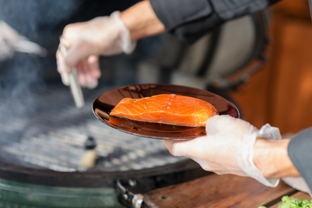 stages of cooking salmon on the grill - the chef puts a piece of fresh fillets on grill rack photo