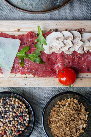 roquette: top view of traditional dish of beef carpaccio on wooden plate with arugula, parmesan cheese, sliced mushrooms and cherry tomatoes on the tablecloth with the decor and spices