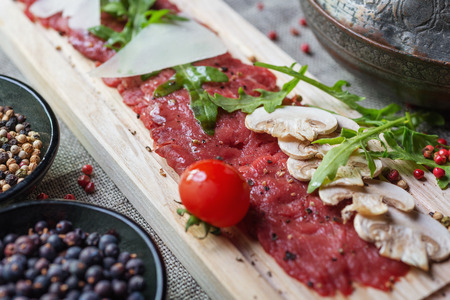 roquette: traditional dish of beef carpaccio on wooden plate with arugula, parmesan cheese, sliced mushrooms and cherry tomatoes on the tablecloth with the decor and spices