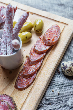 mix of traditional spanish ham, salami, parma ham on grissini bread sticks, marinated vegetables and olives on wooden plate with rustic decor photo