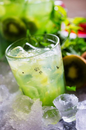 field mint: glass of refreshing tropical kiwi lemonade with ice and mint together with a carafe on the table with a backdrop of the pieces of ice and fresh kiwi shallow depth of field and focus on different parts of the creative composition