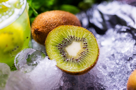 glass of refreshing tropical kiwi lemonade with ice and mint together with a carafe on the table with a backdrop of the pieces of ice and fresh kiwi shallow depth of field and focus on different parts of the creative composition photo