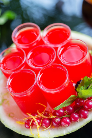 cranberry juice: Set of glasses with alcohol cocktail with cranberry juice on a table in a restaurant with a creative composition of ice watermelon and fresh cranberries. soft focus Stock Photo