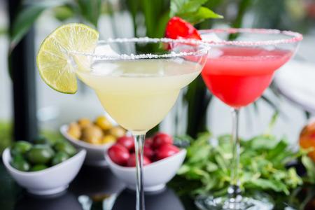 margarita cocktail: una mezcla de los dos cócteles refrescantes brillantes: daiquiri de cal y daiquiri de fresa en una mesa en un restaurante con una decoración creativa de la sal en el borde de la copa con menta fresca y rodajas de limón y bayas. enfoque suave