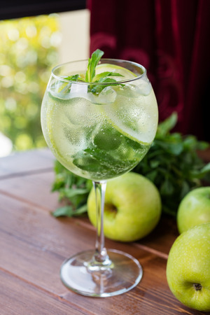 green apple: refreshing glass of cold apple lemonade with mint and ice on a wooden table in a restaurant with a creative decoration of mint leaves and fresh apples. soft focus