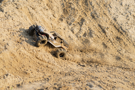 radio activity: radio controlled monster truck performing a trick at high speed jumps over a large pile of sand. soft focus and beautiful bokeh