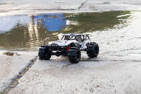 controlled: radio controlled monster truck performing a trick at high speed jumps over a large puddle. soft focus and beautiful bokeh