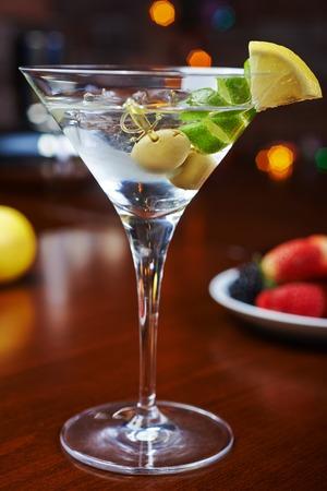 barra: de un delicioso vaso brillante de martinis fr�os con aceitunas en una mesa de madera en un restaurante o un bar con decoraci�n creativa de lima y lim�n. enfoque suave y hermoso bokeh.