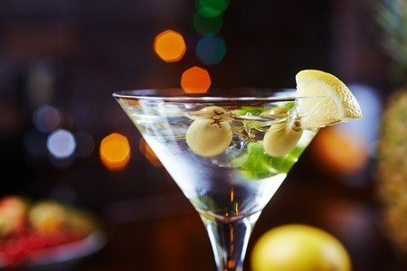 martini: one bright delicious glass of cold martinis with olives on a wooden table in a restaurant or bar with creative decoration lime and lemon. soft focus and beautiful bokeh. Stock Photo