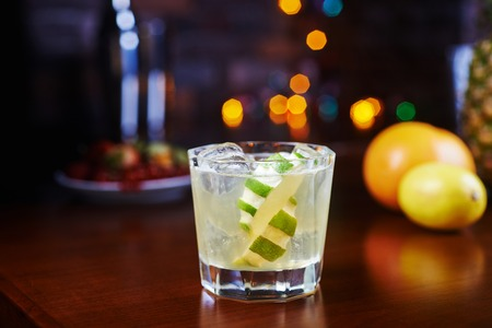 cocteles de frutas: vaso de deliciosos cócteles alcohólicas o limonada con hielo y una rodaja de limón en una mesa en un bar o restaurante con una hermosa bokeh en el fondo
