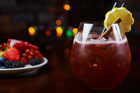 alcohol screwdriver: glass of delicious alcoholic cocktails or lemonade with ice, decoration of fresh berries and a slice of lemon on a wooden table in a bar or restaurant with a beautiful bokeh in the background