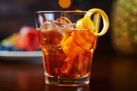 barra de bar: vaso de deliciosos cócteles alcohólicas o limonada con hielo, la decoración de las bayas frescas sobre una mesa de madera en un bar o restaurante con una hermosa bokeh en el fondo. enfoque suave.