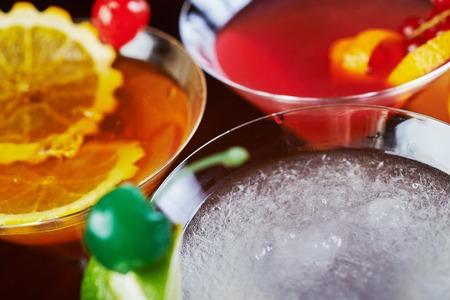 cocteles: vista superior de mezcla brillante delicioso cóctel con decoración de piezas de naranja y una cereza en la mesa en el restaurante con fondos de la luz del disco. hermosa bokeh y enfoque suave. Foto de archivo