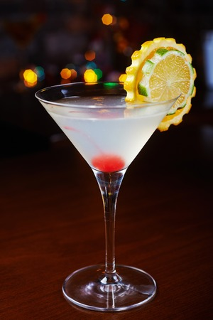 alcohol screwdriver: bright delicious cocktail with decoration of pieces of orange and  cherry at the bottom of the glass on the table in the restaurant with backgrounds from the disco light. beautiful bokeh and soft focus. Stock Photo