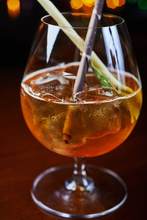 alcohol screwdriver: Bright strong alcoholic cocktail with a creative decoration of chocolate sticks and ice cubes on a table in a restaurant with backgrounds of colored disco lights soft focus and beautiful bokeh. Stock Photo