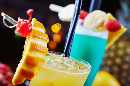 a mix of a few bright tropical cocktails or glasses of lemonade with slices of orange and beautiful decoration on a table in a restaurant with backgrounds of bright colored lights. soft focus.