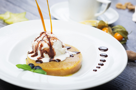 gelati: delicious dessert scoop of ice cream on a hot sherbet served on a white plate on a wooden table in a restaurant