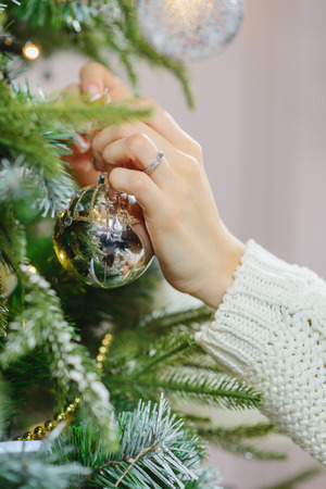 decorates: closeup of a hand of a young girl with Christmas silver ball decorates the Christmas tree for the New Year and Christmas holidays