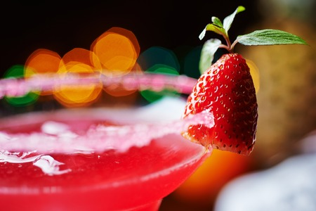 sweet vermouth: close up details of strawberry daiquiri on a table in a restaurant with creative decoration of salt on the edge of the glass with fresh mint and berries. soft focus
