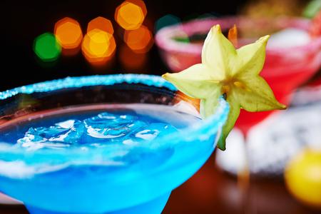 margarita c�ctel: una mezcla de los dos brillantes refrescantes c�cteles margarita azul y daiquiri de fresa en una mesa en un restaurante con una decoraci�n creativa de la sal en el borde del vaso con menta fresca y rodajas de lim�n y bayas. enfoque suave