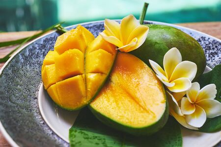 tabel: fresh mango in the plate on a wooden tabel with tropical background. Soft focus.