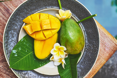 tabel: Top view of fresh mango in the plate on a wooden tabel with tropical background. Soft focus. Stock Photo