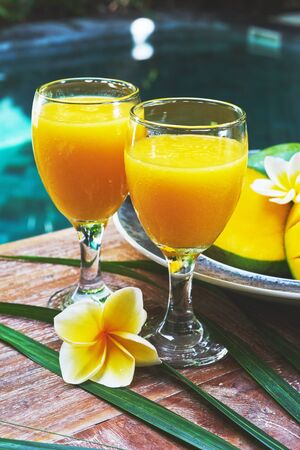 tabel: Glasses of fresh tropical smoothie or mango juice and fresh mango on a wooden tabel and tropical background. Soft focus. Stock Photo