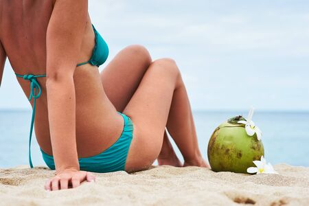tanned body: beautiful young girl with a sports figure and tanned body enjoying the sun on a tropical beach with ocean views and fresh coconut with flowers frangipani Stock Photo