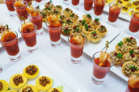 tabel: Food delivery and catering service at the event. Seafood appetizer of shrimp and tomato sauce in a glass on a table with other quick snacks. Meals at the event. Soft focus.