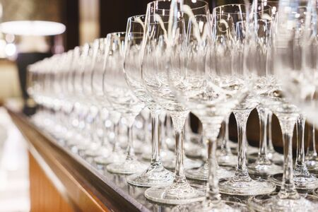 dozens: Rows of dozens of clean glasses for wine and champagne on a rack made the bartender for drinks during the event and celebration. Clean transparent glasses for beverages on the table. Soft focus.