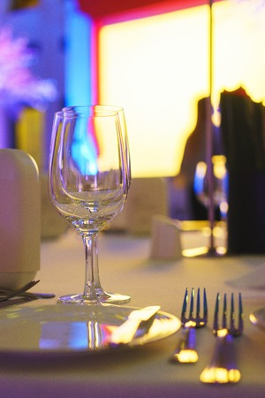 Clean glasses on a table prepared by the waiter for champagne and wine. Several of transparent glasses on a table. Catering for the event preparation, clean glasses for drinks. Soft focus and beautiful bokeh Stock Photo