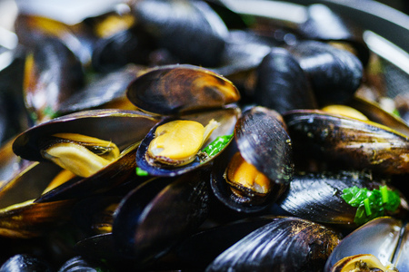 The process of preparation of traditional pasta with seafood. Boiled mussels with spices and herbs close-up. Soft selective focus.