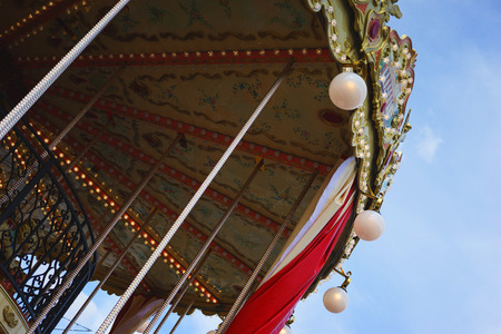 Bright childrens merry-go-round with animals and horses at the spring fair. Entertainment in parks for children and adults - attractions and carousels. Spring walks around the city. Stock Photo