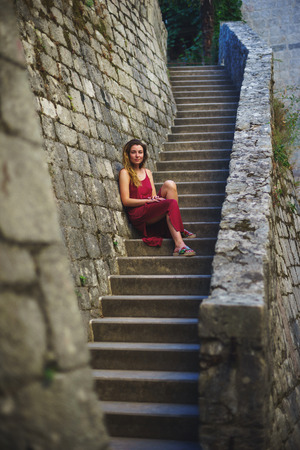 bard: Attractive slender girl in a bard dress is traveling and visiting the sights in an ancient European city. Free beautiful model in the journey. Travel to Montenegro.