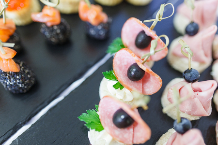 Meals and snacks for guests during the event. Catering. Tapas, canaps, sandwiches, rolls with red fish prepared for the visitors of the event. Close-up and at different angles. Stock Photo