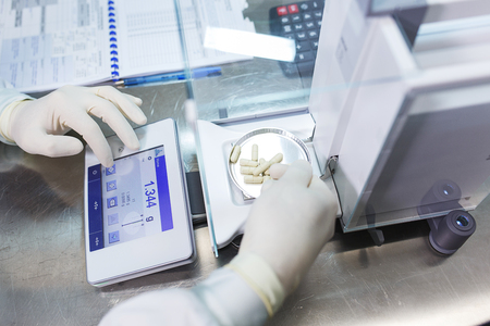 weighs: Pharmacist, a laboratory worker in sterile rubber gloves, weighs the manufactured tablets on the control scales.