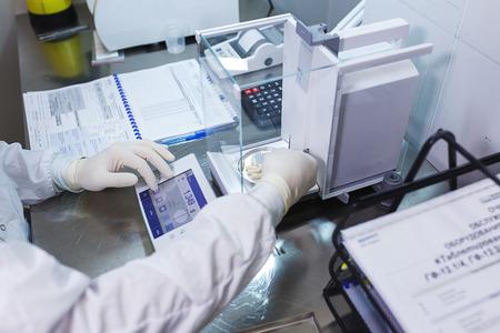 멸균 고무 장갑을 착용 한 실험실 작업자 인 약사는 제조 된 정제를 대조 저울에 무게를 단다.