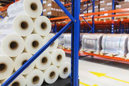 polyethylene film: system of address storage of products, materials and goods in a warehouse. Rolls of polyethylene film in stock. Modern warehouse and storage systems.