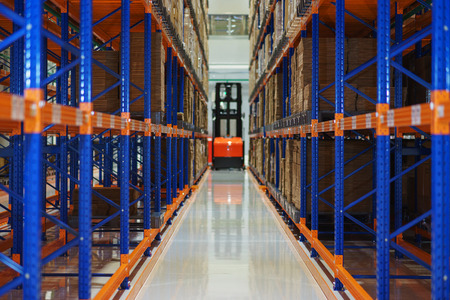 Warehouse and a modern system of targeted storage of products and goods. Electric forklift between large shelving in a modern storage building. Selective focus.