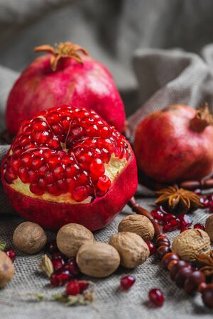 Juicy aromatic pomegranate on the table with a decor of national ornaments. Soft focus and beautiful bokeh.