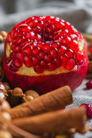 Juicy aromatic pomegranate on the table with a decor. Soft focus and beautiful bokeh. Stock Photo