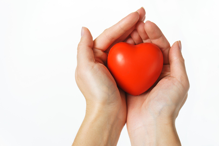 young girl holds a symbolic red heart in the palms. isolated. the concept of caring and generosity.