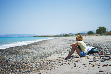 Beautiful girl on the beach watching the sea waves and surf. Travel, weekends and vacations by the sea. Stock Photo