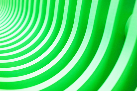 Bright stylish abstract horizontal background of wooden boards painted in bright green color. Alternation of green and white bands. Natural background. Soft focus and shallow depth of field.